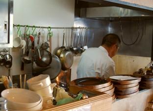 小さな厨房で心を込めて料理するシェフ